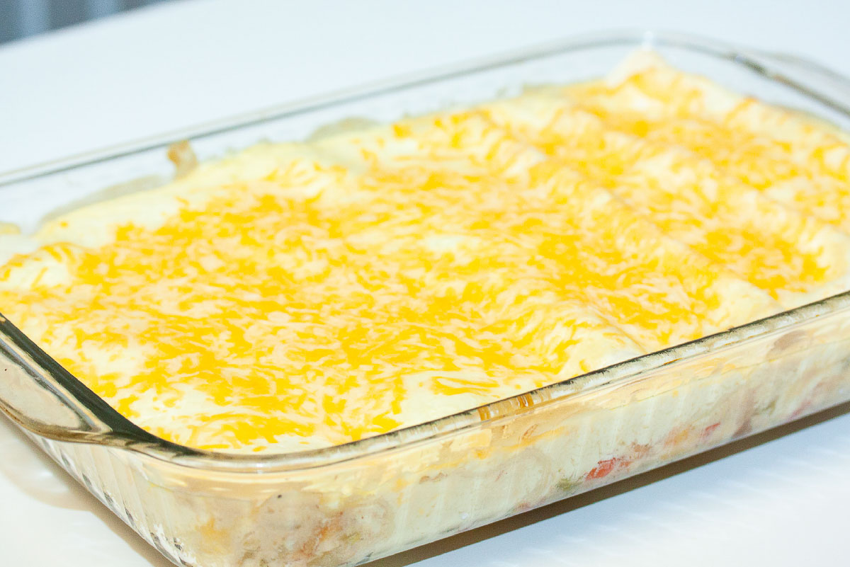 Pan of creamy white enchiladas topped with melted shredded cheese