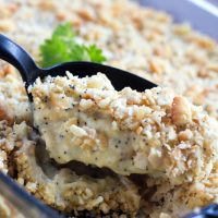 A black spoon is scooping Poppy Seed Chicken Casserole out of a clear glass casserole dish.
