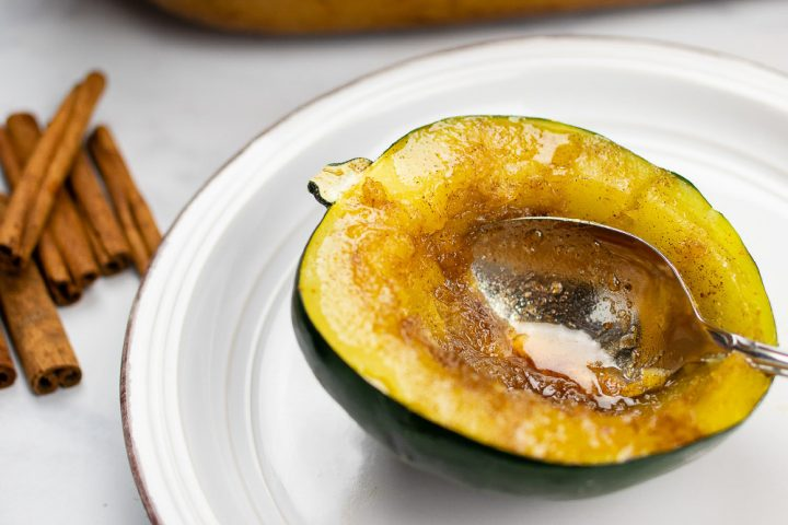 Half of a cooked acorn squash topped with a butter, sugar and cinnamon mixture plated with a serving of poppy seed chicken casserole and seasoned green beans