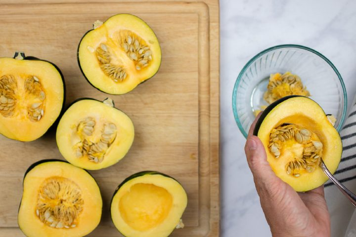 an acorn squash split in half with seeds intact and a spoon scooping the seeds