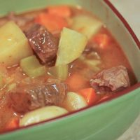 Green bowl with cooked beef cubes, potatoes, carrots, and celery in a tomato-based sauce