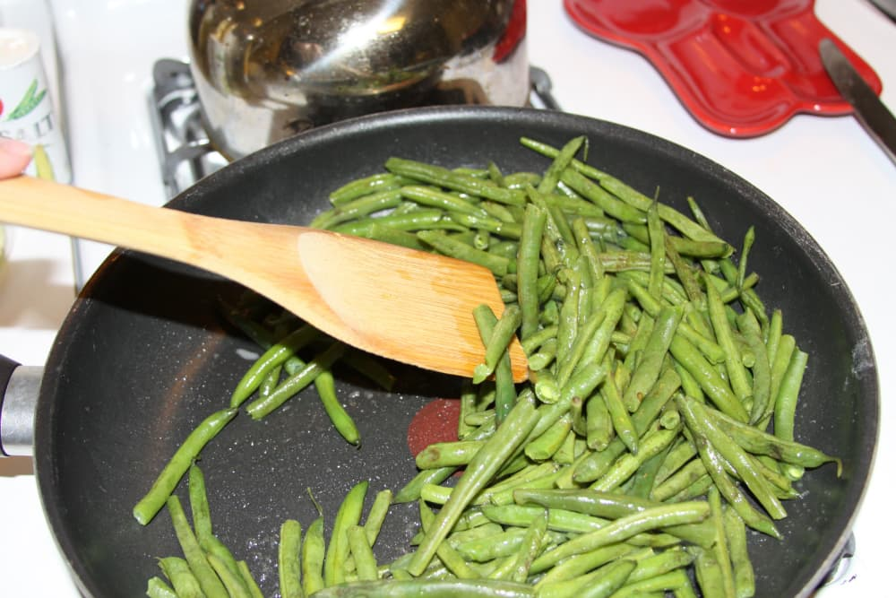 green beans being sautéed in a black frypan