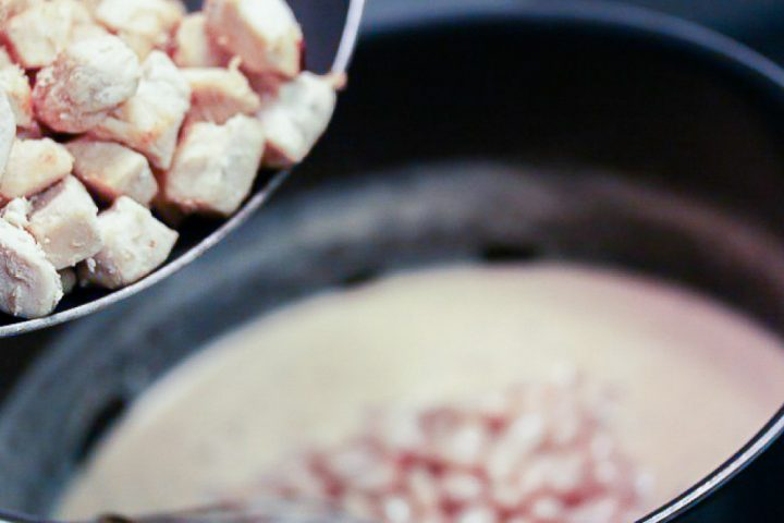 A spoon full of diced cooked chicken being added to a soup pot.