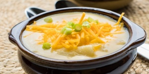 potato soup garnished with cheese and green onion in brown crock