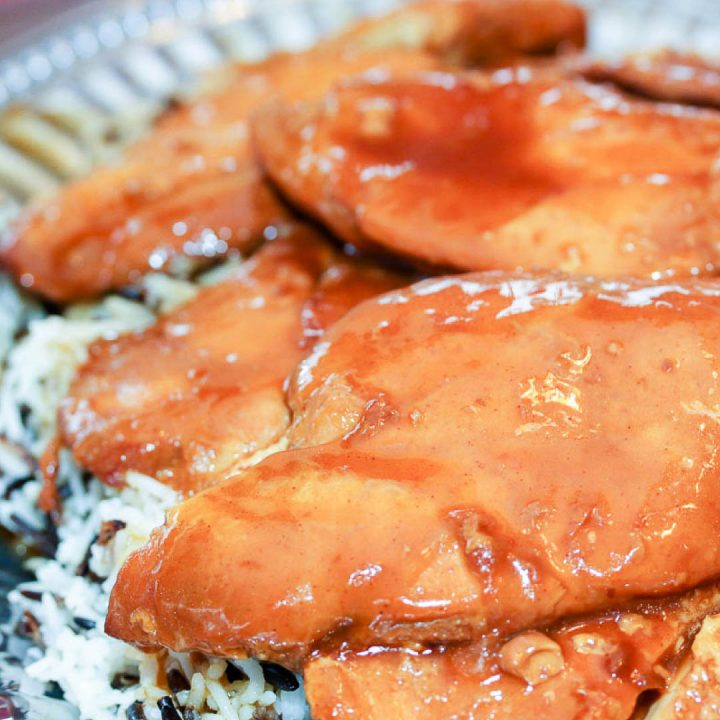 Chicken breasts glazed with French dressing, on a bed of rice on a platter.