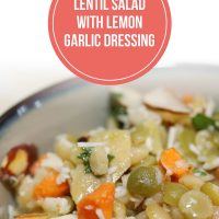 Lentils, carrots, artichokes, and almonds in a bowl topped with dressing and shredded parmesan cheese, garnished with parsley; text Lentil Salad with Lemon Garlic Dressing - Add Salt & Serve logo