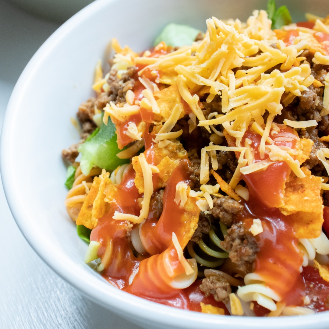 Bowl of seasoned ground beef, spiral pasta, lettuce, halved tomatoes, nacho cheese Doritos, and French salad dressing with shredded cheddar cheese on top