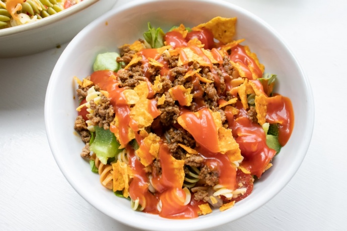 Bowl of seasoned ground beef, spiral pasta, lettuce, halved tomatoes, nacho cheese Doritos, and French salad dressing