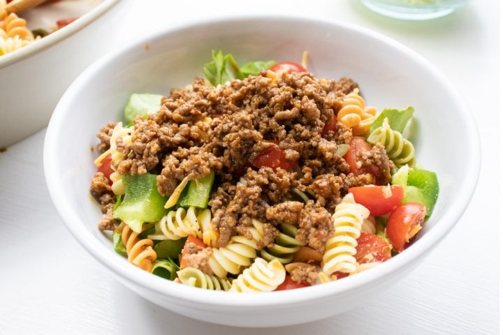 Bowl of seasoned ground beef, spiral pasta, lettuce, and halved tomatoes