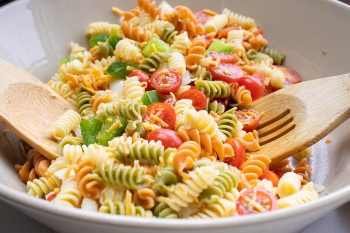 Multi-colored rotini noodles in a bowl with chopped tomatoes and bell peppers and wooden salad spoons.