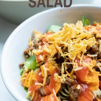 Bowl of seasoned ground beef, spiral pasta, lettuce, halved tomatoes, nacho cheese Doritos, and French salad dressing with shredded cheddar cheese on top with text Taco Mac Salad Add Salt & Serve