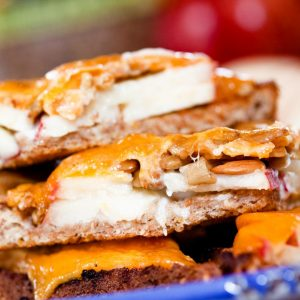 Image of bread with mayo, apple slices, and sunflower seeds topped with melted cheddar and text Open-faced Apple Cheddar Melt Sandwich