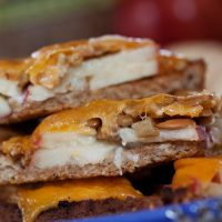 Image of Open-faced Apple Cheddar Melt Sandwich with bread, mayo, apple slices, sunflower seeds, and cheddar melted on top