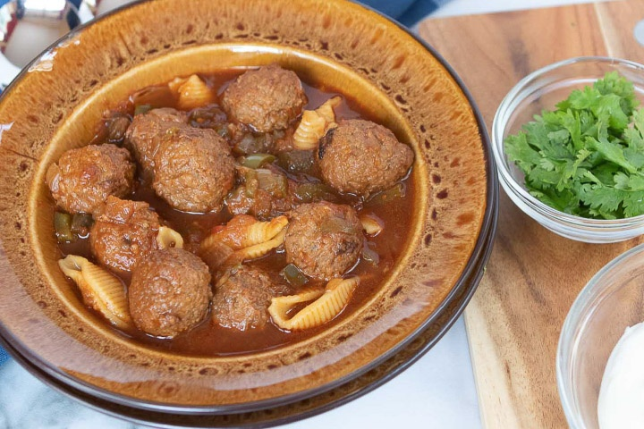 Photo is a brown soup bowl with meatball soup, beside a cutting board. On the cutting board are two clear glass bowls with parsley and sour cream.