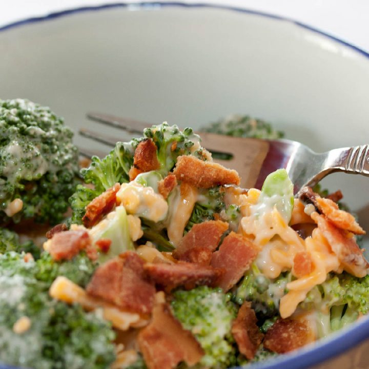 Broccoli, shredded cheddar cheese, bacon bits, and mayonnaise in a bowl with a fork.