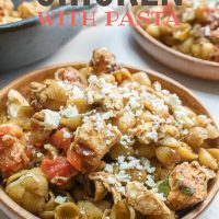 Bowl of shell pasta with tomatoes, feta cheese, and balsamic vinegar with text Mediterranean Chicken with Pasta