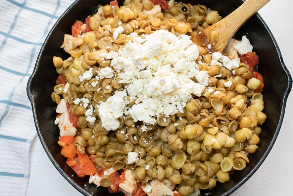 Cast iron skillet with shell pasta, tomatoes, onions, feta cheese, and balsamic vinegar