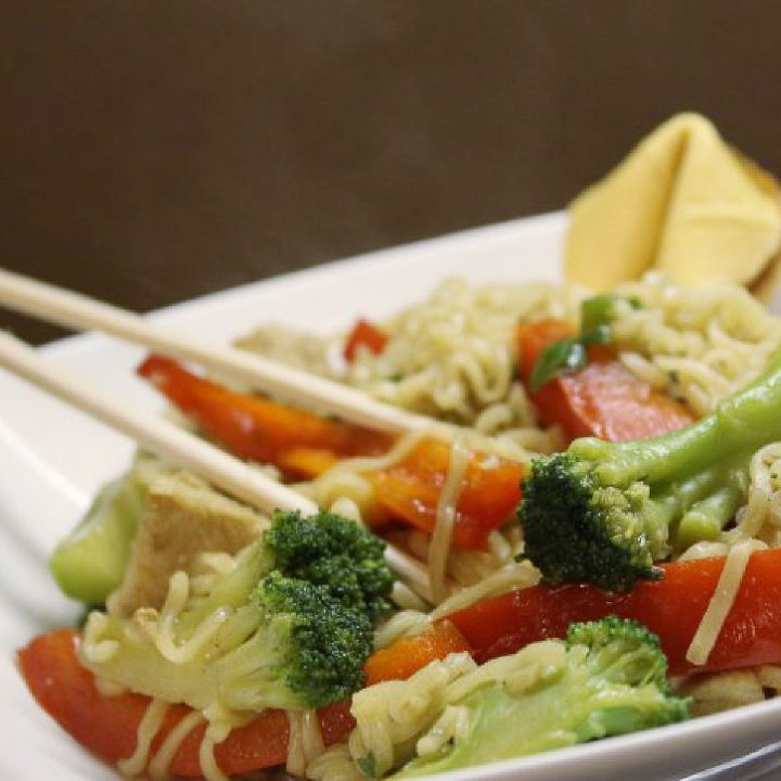 Ramen noodles, broccoli, and bell pepper strips in a bowl with chopsticks.