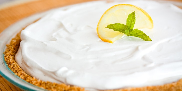 Pie with white frozen filling and graham cracker crust garnished with a twisted slice of lemon and mint with text Frozen Lemonade Pie Menus4Moms