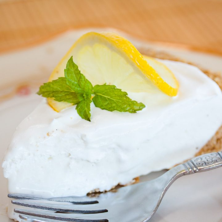 a slice of frozen lemonade pie garnished with a twisted slice of lemon and mint, text Frozen Lemonade Pie Menus4Moms
