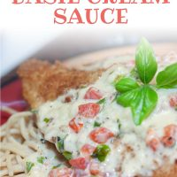 Breaded chicken breast covered with a cream sauce and resting on a plate of spaghetti. Text is Chicken with Basil Cream Sauce - Add Salt & Serve logo