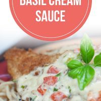 Breaded chicken breast covered with a cream sauce and resting on a plate of spaghetti. Text is Chicken in Basil Cream Sauce - Add Salt & Serve logo