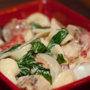Red square bowl with orecchiette pasta, sliced onion, chopped bacon, roasted bell peppers, cooked spinach, and Alfredo sauce.