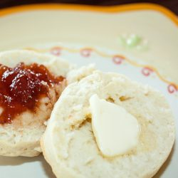 Biscuit cut in half with butter on one half and fruit preserves on the other half on a yellow and white plate