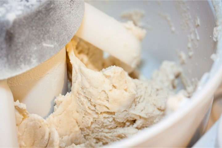 Stand mixer with dough paddles and biscuit dough being mixed