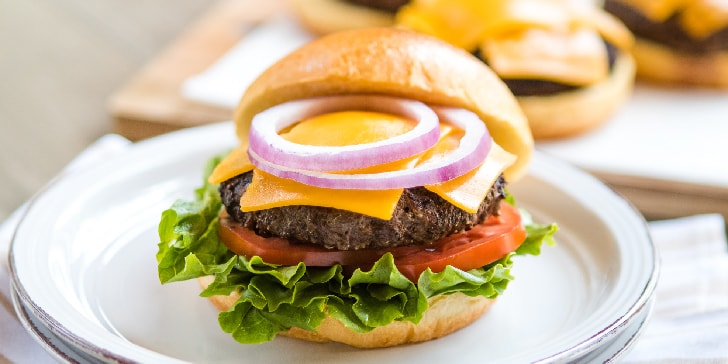 Hamburger on brioche bun with lettuce and tomato underneath patty and cheddar cheese slices and rings of red onion on top of patty. Bun lid is propped at the back and additional cheese-topped patties on bun bottom are in background.