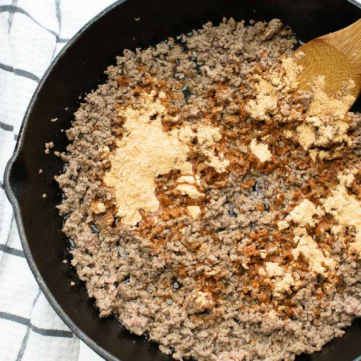 Overhead shot of ground beef in a cast iron skillet with taco seasoning on top