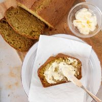 Overhead shot of a loaf of zucchini bread with a slice being spread with clotted cream and text Zucchini Sweet Bread, recipes and ideas using zucchini Menus4Moms