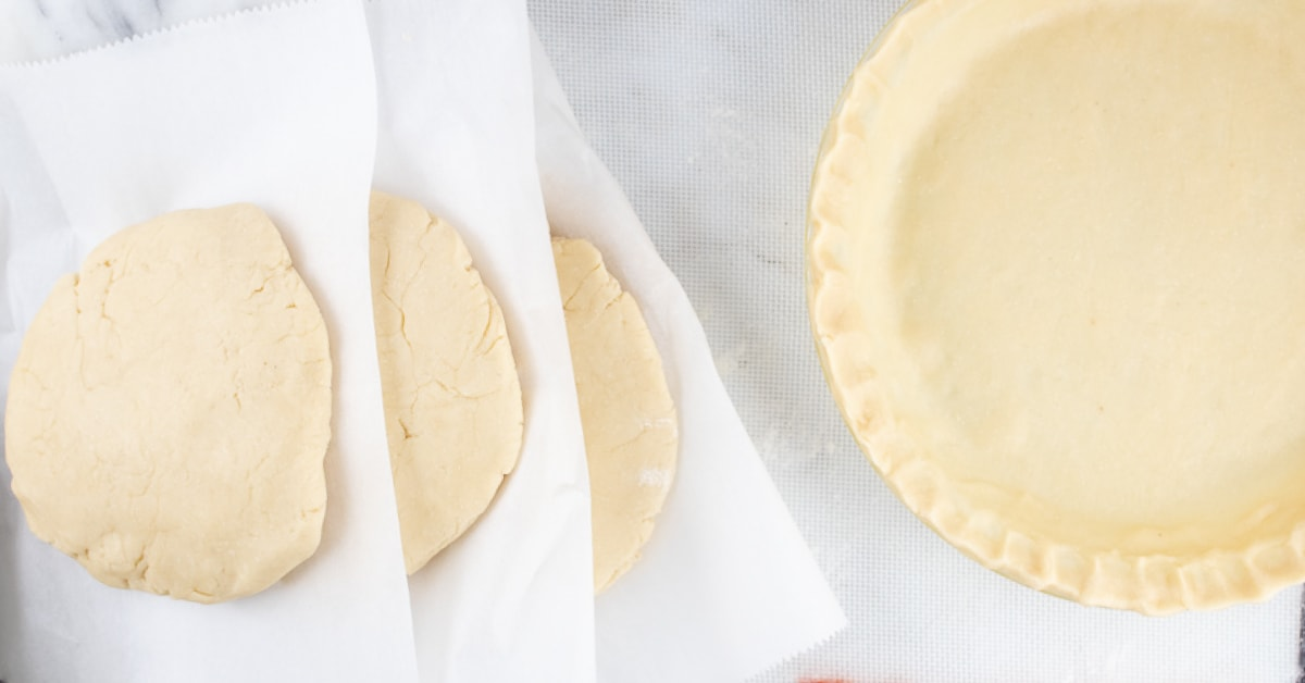 Overhead image of unbaked pie crust in a pie pan to the right and thick circles of pie crust dough stacked with parchment paper in between ready for the freezer