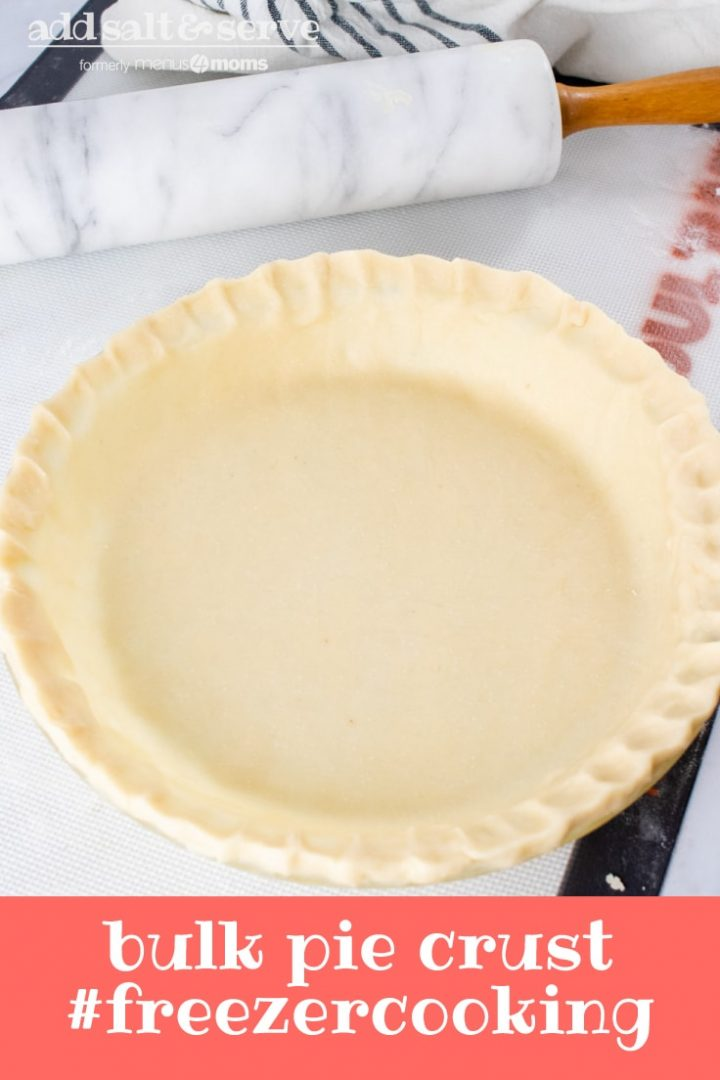 Unbaked pie crust in a pie pan with a marble rolling pin and flour sack towel in the background and text Bulk Pie Crust #freezercooking