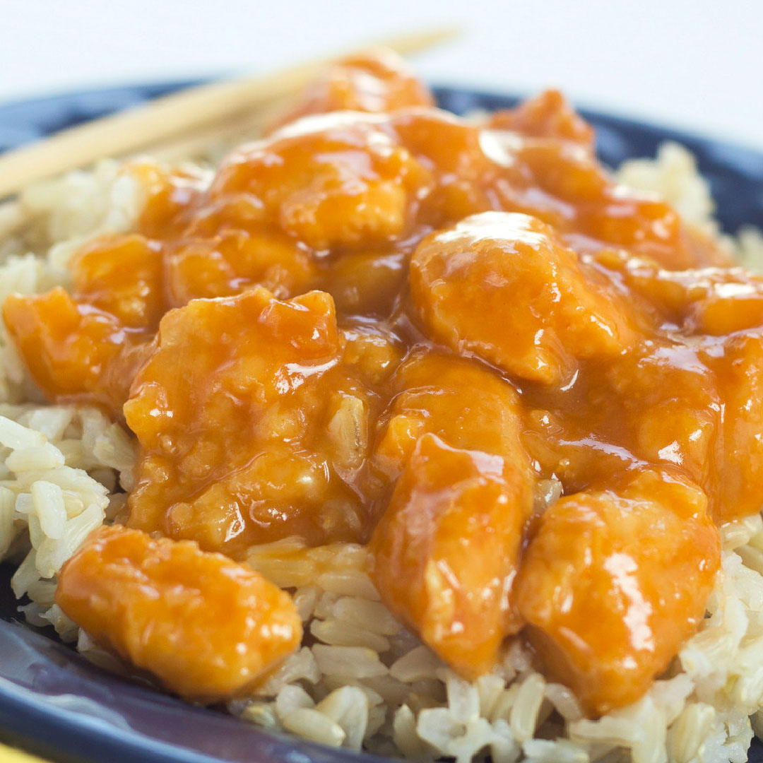 Crockpot Orange Chicken on a bed of rice with chopsticks