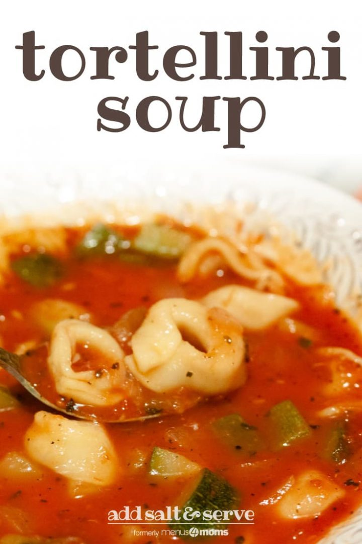 White bowl with tortellini zucchini soup. Soup is red with tortellini and diced zucchini. There is a spoon lifting a bite of soup that includes two tortellini. Text tortellini soup add salt & serve formerly menus4moms