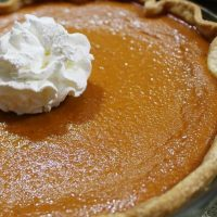 Baked pumpkin pie garnished with whipped cream