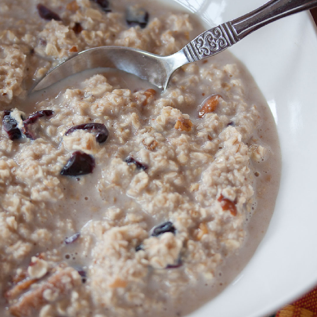 Oatmeal with raisins and nuts in a white bowl with spoon
