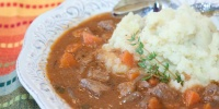 Beef and Guinness Stew over mashed potatoes in a white bowl with a spoon and a sprig of thyme