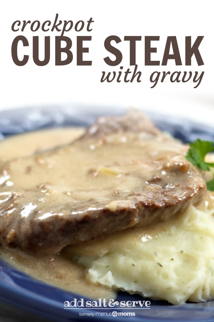 Cube steak over mashed potatoes covered with gravy, all on a blue plate and garnised with parsley