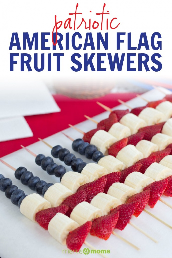 Blueberries, strawberries, and bananas threaded on bamboo skewers in the design of an American flag with text American Flag Fruit Skewers Add Salt & Serve