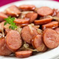 Sliced kielbasa with sliced onions on a white plate.