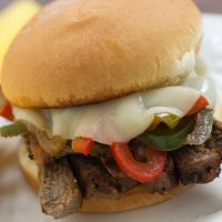 Close up photo of Steak Sandwich with Cheese and Peppers on a white plate