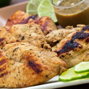 Grilled chicken on a square plate, garnished with lime slices. A small clear glass cup of Dijon basil lime dipping sauce is on the plate.