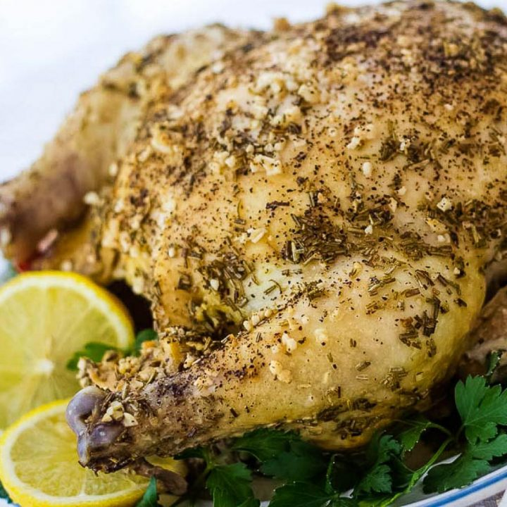 Whole roasted chicken with a dried rosemary and minced garlic rub on a white plate, garnished with lemon slices and parsley.
