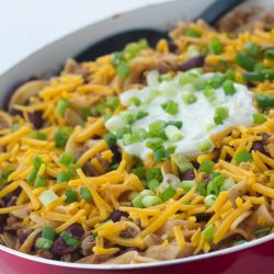 Kidney beans, ground beef, and egg noodles topped with shredded cheddar cheese, sour cream, and chopped green onions, in a skillet.