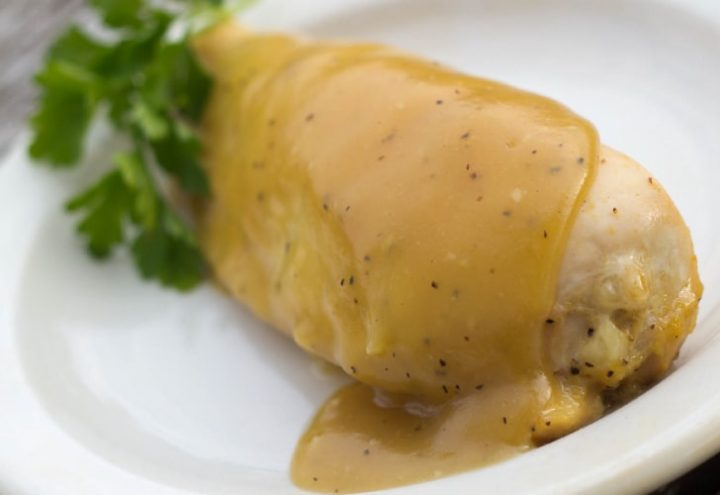 White plate with chicken breast topped with a Dijon sauce.