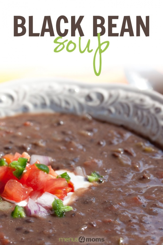 A white shallow bowl with Black Bean Soup garnished with sour cream, diced tomatoes, diced red onion, and fresh cilantro and text Black Bean Soup Menus4Moms