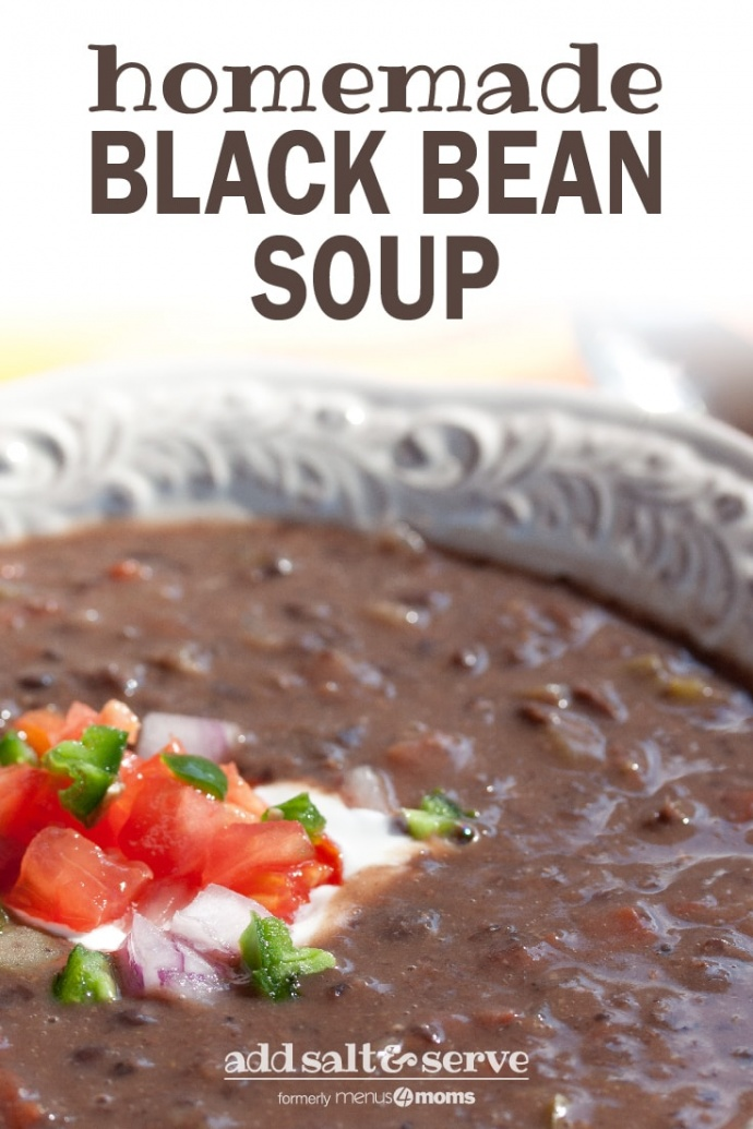 A white shallow bowl with Black Bean Soup garnished with sour cream, diced tomatoes, diced red onion, and fresh cilantro and text Black Bean Soup add salt & serve formerly Menus4Moms
