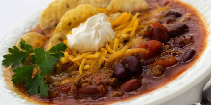 White bowl filled with soup of beans, tomatoes, and beef, topped with shredded cheddar cheese, tortilla chips, and sour cream, garnished with cilantro.